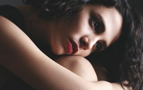 Girl looking sad while hugging her knees