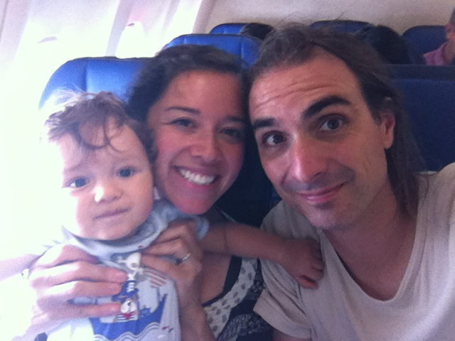 Baby, mom, and dad, smiling and sitting inside a plane. Baby plane travel guide.