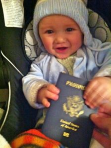 Baby holding a passport ready to travel on a plane. Baby plane travel guide.