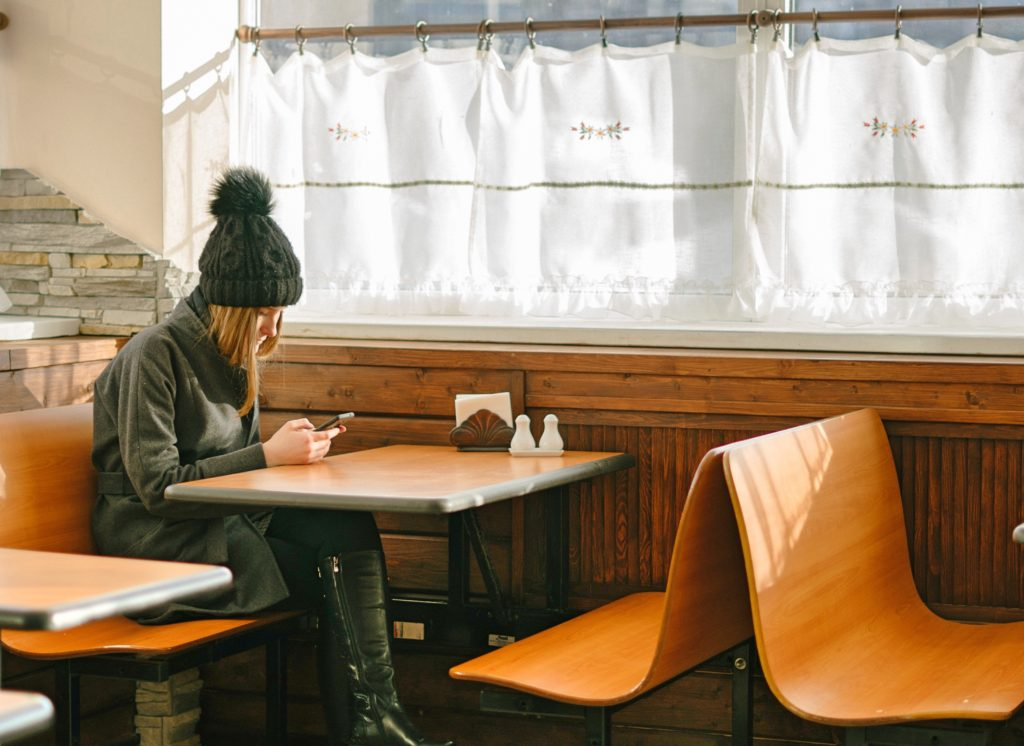 Relocating Tips - Girl looking at her phone at a diner.