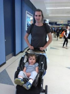 Dad pushing baby in a stroller through airport